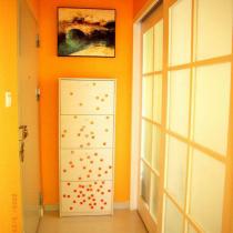 """入户门口的小走廊,白色的鞋柜上给偶贴了些马赛克,上方是朋友亲笔画的名为""""水乡""""的油画;旁边是书房的白色木门"""