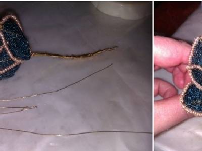 用同样的步骤多做几片花瓣,然后拧在一起。还可以剪出一段一段的铁丝,穿上一颗珍珠,拧出主干,一起束在花瓣中。