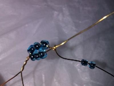 一边长的铁丝,往下推3颗珠子,把长的铁丝绕到主脉络(短铁丝)珠子的上边,然后将长铁丝缠绕在主脉络(短铁丝)上。如上图所示。