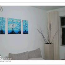 沙发背景墙上的装饰画与墙角的枯枝