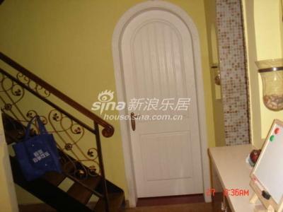 来到一楼了,白色圆拱门后面是客卧。