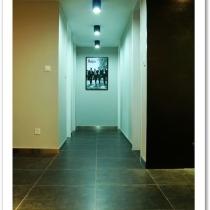 玄关看完了就是走廊了,用了明装的黑色筒灯,走廊的墙刷成了灰色,不是很深。房间的门是白的,为了追求风格,门做到顶,踢脚线用的是不锈钢的。地砖是灰黑色的,黑的多,灰的少。走廊镜头是60年代披头士的海报,也