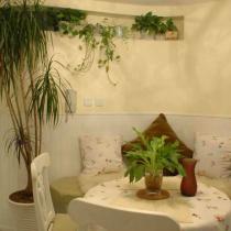 白色曲线纹样靠背的餐桌椅,搭配上了深草绿色的椅垫,与沿墙定做的弧形沙发和谐组合;碎花的餐桌布和沙发小靠枕点缀着不宽敞的餐厅空间。餐厅中弥漫着田园的清新气息,给人带来轻松舒适的氛围,仿佛一踏入这里就可以闻到淡淡草味和浓郁的花香