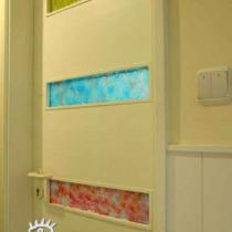 卫生间的门是根据设计定制加工的,选定了门样式另外搭配了3块琉璃玻璃镶嵌,红、黄、蓝三种色调赋予了白色门板艺术的多彩绚烂气息