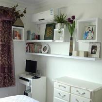 卧床对面的小小办公桌与收纳柜,白色木质,与卧室的整体风格十分搭配。