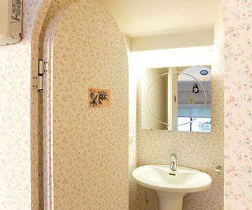 弧形拱门设计,搭配门板上嵌入自国外带回的造型图画磁砖,以及小碎花壁纸,连小小浴室也洋溢着异国风情
