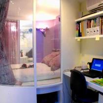 从阳台望去,圆柱的玻璃造型睡眠区依旧是居室的出彩点;倚墙安置的一块台面和二块搁板简约而流畅的造就了家中的办公空间