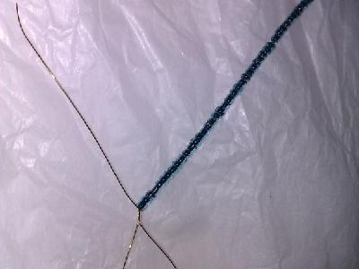 """往长的""""尾巴""""上穿入绿色珠子,铁丝上至少有三分之二的部分穿满珠子。"""