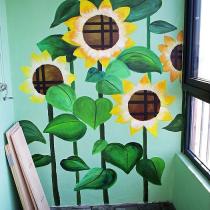 阳台上也被刷上了绿色,还请人画了这些向日葵,如果在向日葵下面放个吊起来那种藤摇椅会不会很惬意呢。。。