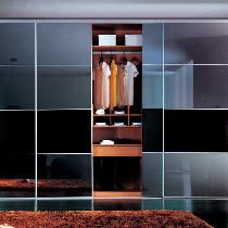 适合空间特点:在卧室一端已经专门划分了衣帽间区域。方案分析:玻璃门制造通透的感觉,暗色玻璃可以阻挡一些衣帽间内部的凌乱。内部结构设计要考虑完全,悬挂、平放、抽屉、小隔间等都要适当选择。外观提示:斜屋顶下,一般采光不会很理想,所以建议选择浅色衣柜面板。推荐产品:联邦高登灰色镜面玻璃趟门SG806,冷酷的外观下,有着无限温情。