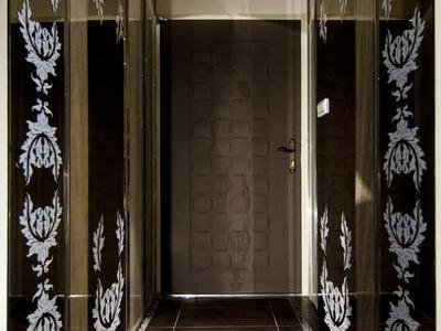 进入私人场域的走道,设计师以风化木将门片隐藏其中,头顶用长型镜面做出格栅造型,反射室内风光,下方打光的吧檯旁,贴上马赛克,营造摩登时尚感。