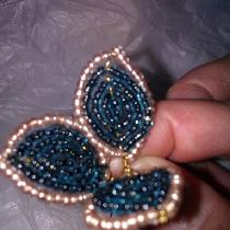 继续往长铁丝上穿入白色珠子,数量至少要比花瓣最外一圈的绿色珠子多。然后用相同的方法绕在主脉络上,形成花瓣的外轮廓。剩下的铁丝在花瓣下端拧在一起做花柄。