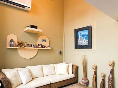将客厅上方挑高的空间设计手法,搭配芥末绿墙面、藤制沙发,消弥小坪数局促感