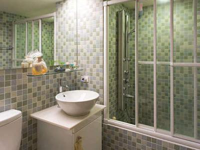 打开拱门造型的浴室门后,全室贴上蓝、绿、灰相间的马赛克砖,散发悠然自在的清爽氛围。在房子还在基础建设时,就先请建商在浴室贴上选用的马赛克磁砖,并要求做出矮墙,直接在矮墙上安装浴门,如此既有干湿分离的效