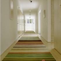 大户型或是别墅的家庭,常常有这样的玄关格局:又长又狭窄的的走道。大胆的为其铺设合适长度与宽度的超狭长型条纹地毯,颜色上选择清新的彩色条,给玄关纳入一道道靓丽的彩虹。