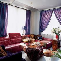 色彩明快的红色沙发避免了浅色墙壁和水泥地面带来的沉闷与疏离感,搭配淡紫色的窗帘既活泼又大方
