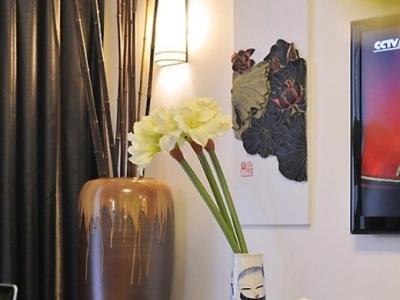 电视墙:两幅水墨画分别挂在电视两边,电视桌上同样摆放着瓷器装饰,一边是CD柜,一边是大的花瓶装饰,增添些现代感。