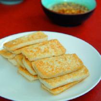 """【脆皮豆腐】这道脆皮豆腐,原汁原味煎制而成,佐以蘸汁,风味独特。豆腐是我国炼丹家——淮南王刘安发明的绿色健康食品,时至今日,已有二千一百多年的历史。豆腐营养丰富,有""""植物肉""""之称,其蛋白质可消化率在90%以上,比豆浆以外其它豆制品高故受到普遍欢迎,一天进食两小块豆腐,即可满足一个人一天钙的需要量。豆腐为补益清热养生食品,常食可补中益气、清热润燥、生津止渴、清洁肠胃。"""