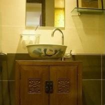 洗手间的脸盆,下面的小柜子也是实木的。卫生间的地面是青石板
